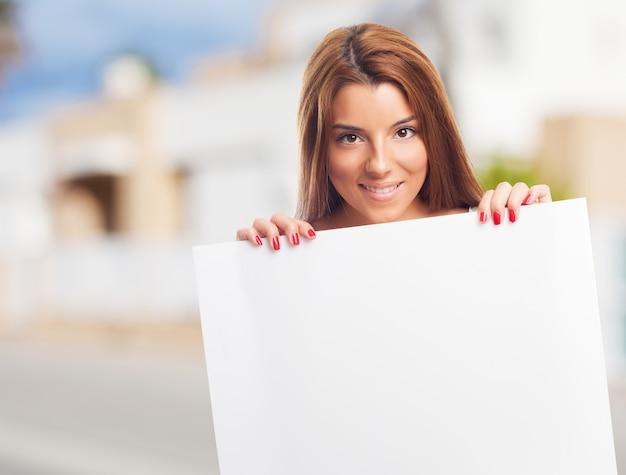 白いプラカードを持つ魅力的な女性