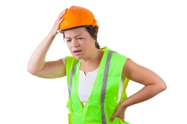 안전 재킷과 노란색 헬멧을 쓴 매력적인 여성 노동자는 흰색 바탕에 요통을 앓고 있다
