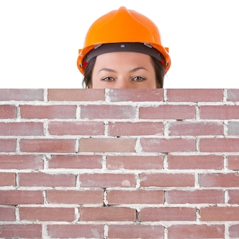 白い背景の上のあなたのデザインのための空きスペースと空白のレンガの壁の後ろに安全黄色のヘルメットの魅力的な女性労働者