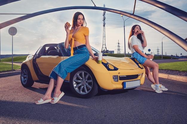 매력적인 여성들은 햄버거를 먹고 노란색 자동차의 두건에 기대어 종이 컵에 음료를 들고 있습니다.