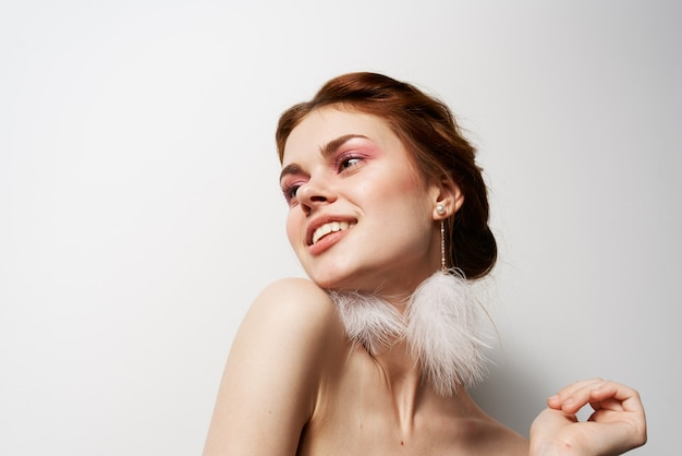 매력적인 여성 푹신한 귀걸이 누드 어깨 화장품
