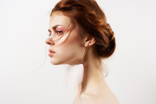 Attractive women fluffy earrings nude shoulders cosmetics