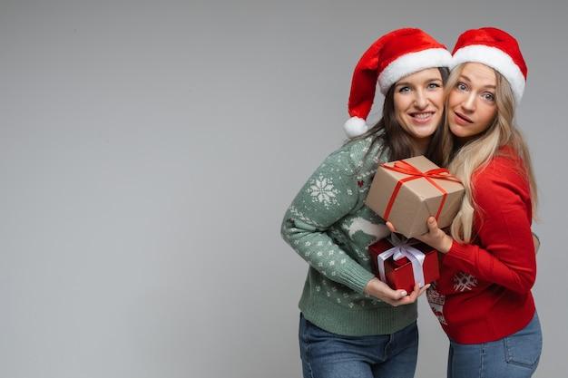 빨간색과 흰색 크리스마스 모자를 쓴 매력적인 여자 친구들은 서로에게 선물을 주고 미소를 짓습니다