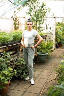 温室でプラスチック製の鉢を保持しているカジュアルな服を着た魅力的な女性の庭師。