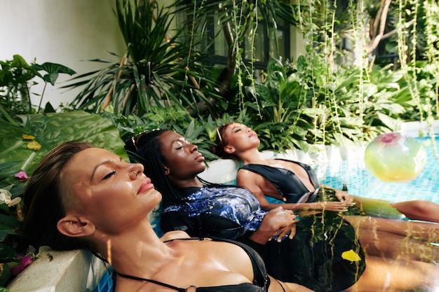 Attractive women relaxing in outdoor pool