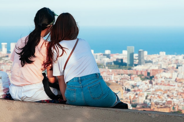 Привлекательные женщины наблюдают за горизонтом барселоны, сидя на вершине холма старый бункер. вид сверху на городские улицы и гавань. каталония, испания. наслаждайтесь концепцией путешествий