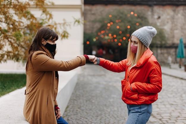 保護用の医療用マスクを着用し、通りに立っているときにお互いに拳をぶつけ合う魅力的な女性。パンデミック時の代替挨拶。