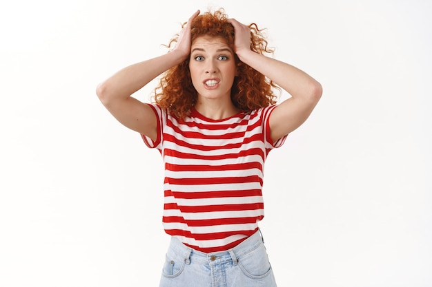 Attractive worried puzzled and concerned young redhead curly woman grab head panic clench teeth look shocked troubled camera confused what do how solve bad situation