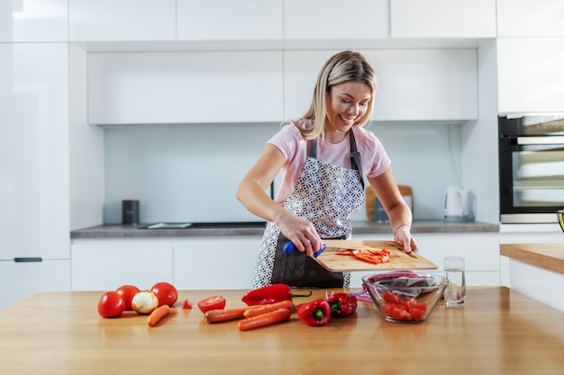 キッチンに立って、みじん切り野菜をボウルに入れてエプロンで魅力的な価値のある笑顔の白人金髪女性。