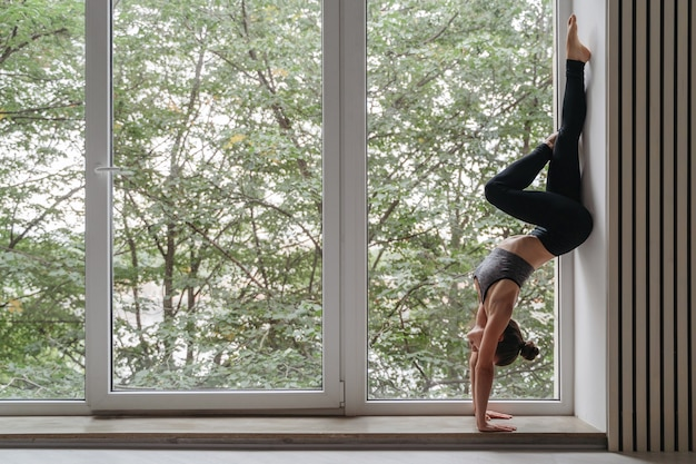 Attractive yoga girl standing on hands against wall in daylight near big window