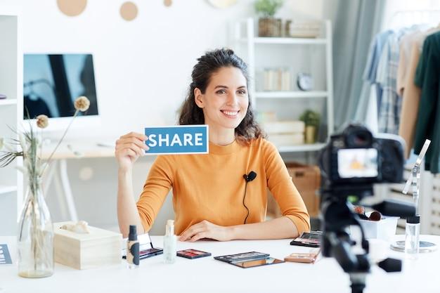 Привлекательный молодой взрослый блоггер красоты сидит за столом, держа знак печати, горизонтальный портретный выстрел
