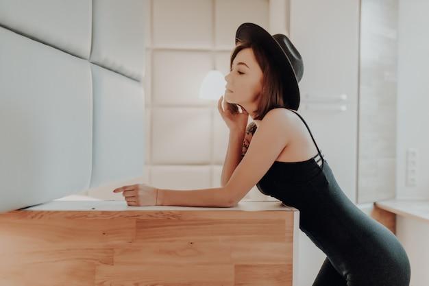 魅力的な若い大人のブルネットの女性はファッションのアパートで黒のドレスでポーズをとってください。