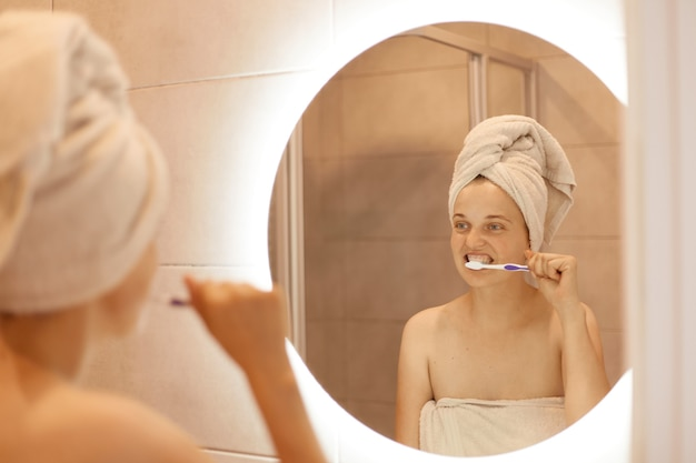 Attractive young adult female with white towel on her hair posing in front of the mirror in the bathroom and brushing her teeth, hygiene procedures after taking shower.