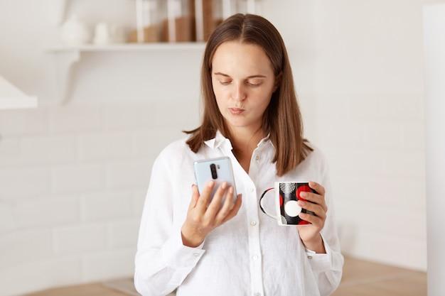 魅力的な若い大人の物思いにふける女性は、スマートフォンを手に立って、ソーシャルネットワークでニュースを読んだり、キッチンでコーヒーやお茶を飲んだり、白いカジュアルなスタイルのシャツを着ています。