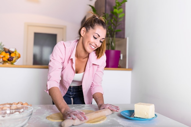 Attractive young adult woman lady housewife baker holding pin rolling dough