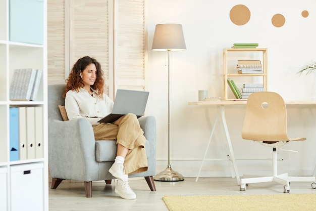 Attractive young adult woman sitting in armchair doing her job using laptop and internet