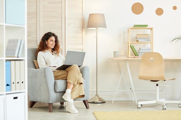 Привлекательная молодая взрослая женщина, сидящая в кресле, делает свою работу, используя ноутбук и интернет