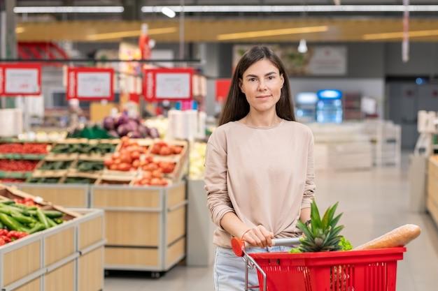 店の通路でショッピングカートと一緒に立っているカジュアルな服を着ている魅力的な若い大人の女性