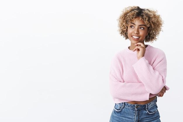 Attraente giovane studentessa afro-americana con i capelli biondi che tiene la mano sul mento e guarda felice nell'angolo in alto a sinistra mentre pensa, posa pensierosa soddisfatta dell'idea mi è venuta in mente