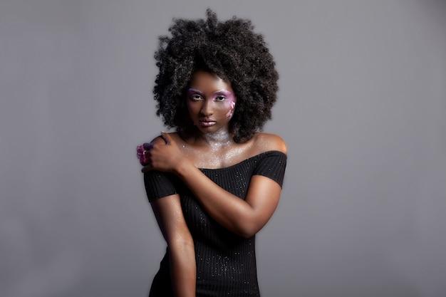 Attraente giovane donna afro-americana con pelle liscia che indossa un bel trucco