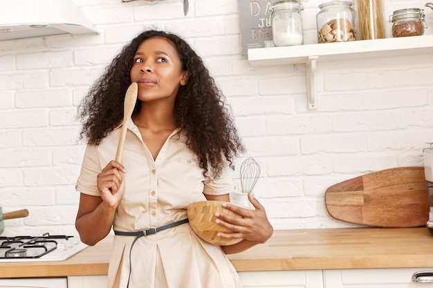 Attractive young african american housewife in beige dress standing in kitchen with utensils and wooden spoon having pensive facial expression, thinking what to cook for dinner. cuisine and food