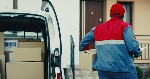 Привлекательный молодой афроамериканец почтальон в красном костюме и кепке вынимает перку из фургона и идет к дому, чтобы доставить его. на улице.