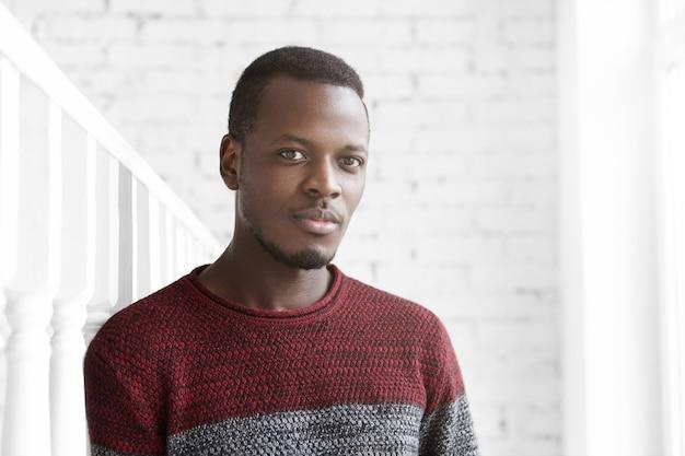 カジュアルなカメラ目線の服を着て魅力的な若いアフリカ系アメリカ人男性