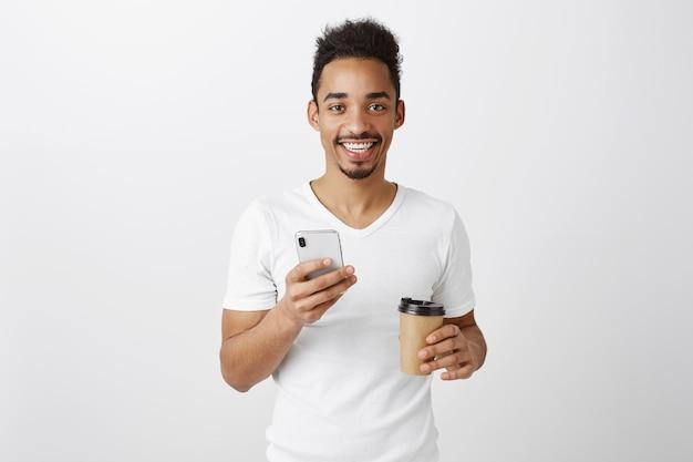 Привлекательный молодой афро-американский мужчина выглядит довольным, держит мобильный телефон и пьет кофе на вынос