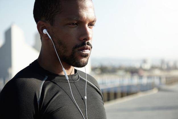 魅力的な若いアフリカ系アメリカ人ランナーまたはジョガーは、朝の太陽の下で屋外で運動する黒いスポーツウェアに身を包んだ。彼のイヤホンを使用してトレーニングのためのやる気を起こさせる音楽を聞いてハンサムな黒人男性