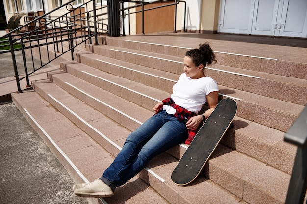 Attractive young african american woman in casual clothing posing on stairs with skateboard and enjoying sunny day
