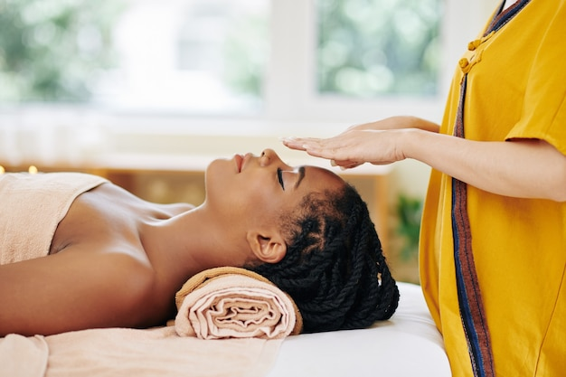 Attractive young african-american woman getting reiki healing therapy in spa salon