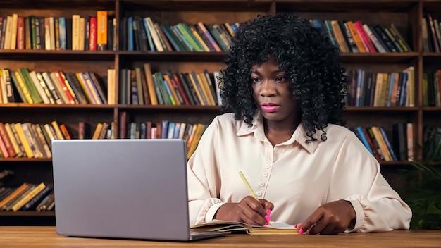 세련된 셔츠를 입은 매력적인 젊은 아프리카계 미국인 여성은 책장 근처 테이블에 앉아 있는 현대적인 노트북을 들여다보며 메모를 씁니다.