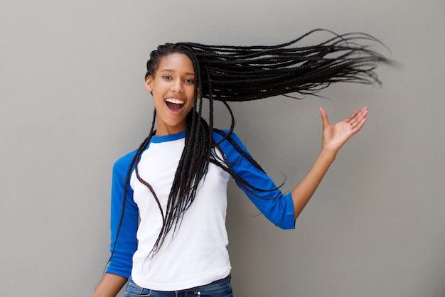 회색 배경에 긴 꼰 머리를 가진 매력적인 젊은 아프리카 계 미국인 여자
