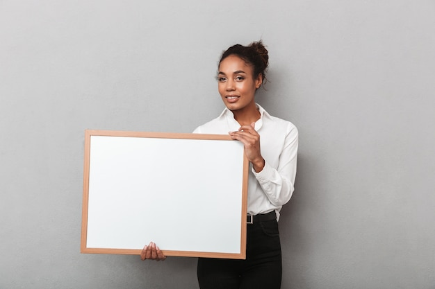 Attractive young african business woman wearing shirt standing isolated, holding blank board