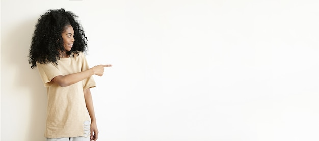 Attractive young african female with afro hairstyle posing indoors at white wall, looking away with cheerful expression, pointing her index finger at copyspace