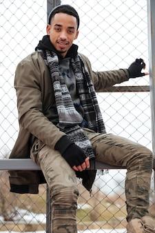 Шляпа и шарф привлекательного молодого африканского человека нося