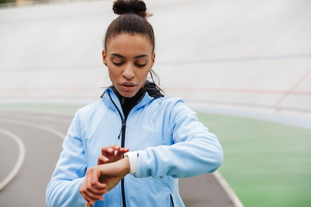 Attractive young african sportswoman resting after running at the stadium, looking at smartwatch