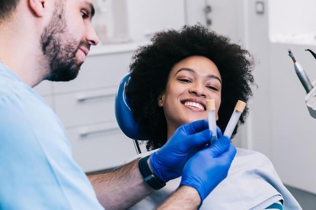 Привлекательной молодой африканской женщине делают омолаживающие инъекции для лица. она спокойно сидит в клинике. профессиональный косметолог заполняет женские морщинки гиалуроновой кислотой.