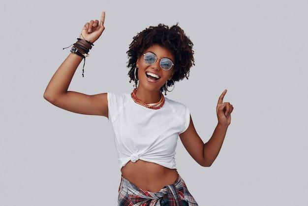 カメラを見て、灰色の背景に立って笑っている魅力的な若いアフリカの女性