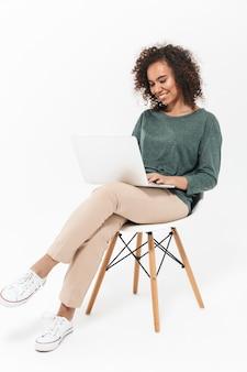 ラップトップコンピューターを使用して、白い壁に隔離された椅子に座っている魅力的な若いアフリカの女性