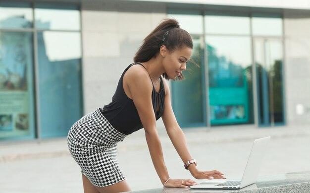 ラップトップを屋外で使う魅力的な若いアフリカ人女性。