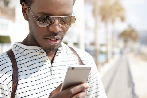 Attraente giovane viaggiatore afroamericano in tonalità di tendenza utilizzando l'app di navigazione sul suo telefono cellulare generico, in cerca di direzione mentre si cammina nella sola città straniera. persone e tecnologia moderna