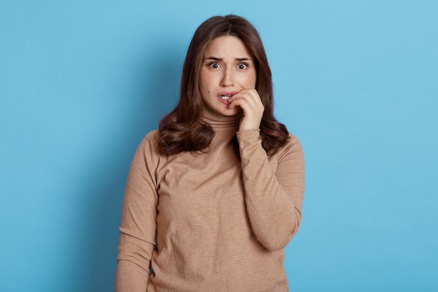그녀의 손톱, 두려움으로 가득 찬 눈, 베이지 색 터틀넥을 입고 파란색 벽에 서있는 매력적인 젊은 불안한 불안한 불안한 신경 여성.