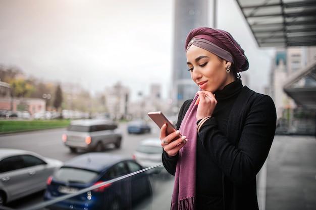 매력적인 젊은 아라비아 여자 전화 호 손을 잡고 보인다.