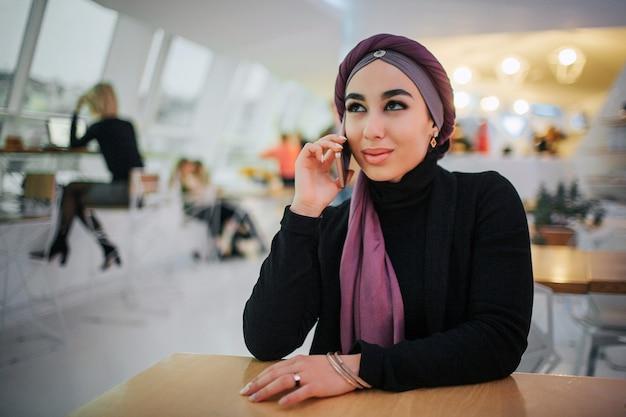 매력적인 젊은 아라비아 여자 카페에서 테이블에 앉아.