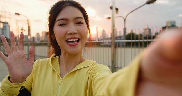 都会でのエクササイズ中に魅力的な若いアジア選手のインフルエンサーレディーがソーシャルメディアの電話アップロードでビデオvlogライブストリーミングを録画しています。朝の通りにスポーツ服を着ているスポーツウーマン。