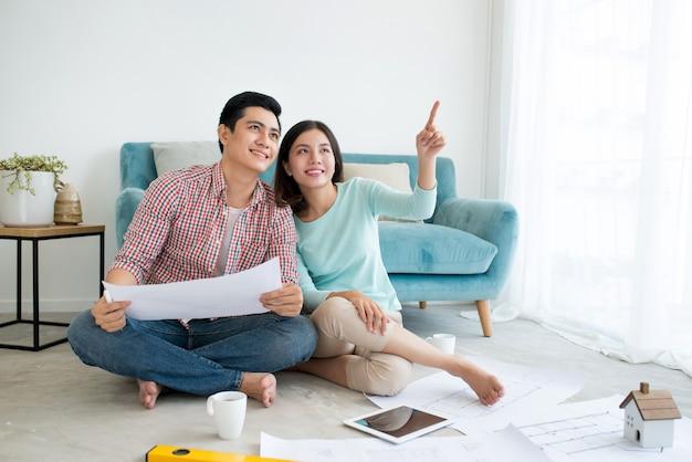 매력적인 젊은 아시아 성인 부부는 새로운 주택 디자인을 계획하고 있습니다.