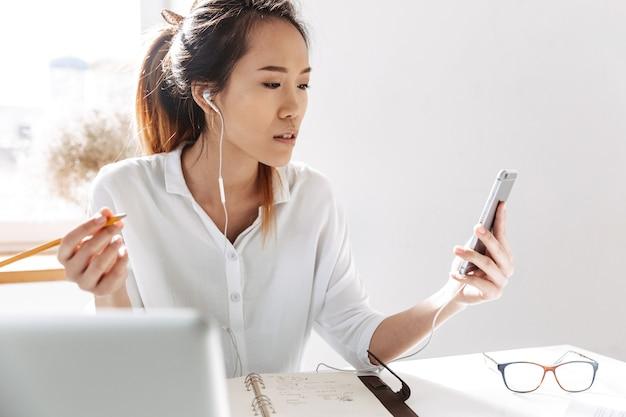 Привлекательная молодая азиатская коммерсантка, сидящая в офисе с портативным компьютером, держащим мобильный телефон, в наушниках
