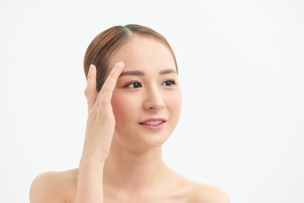 白い背景の上の彼女の顔に触れる魅力的な若いアジアの女の子。ビューティー&スキンケアのコンセプト