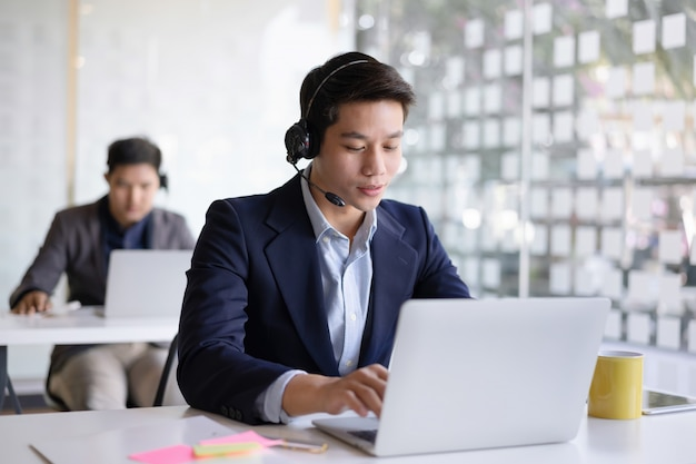 Attractive young asian male call center agent in headset consulting client.